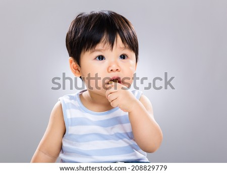 One year old baby boy eat biscuit - stock photo