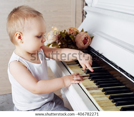 one year old baby boy playing an old piano - stock photo