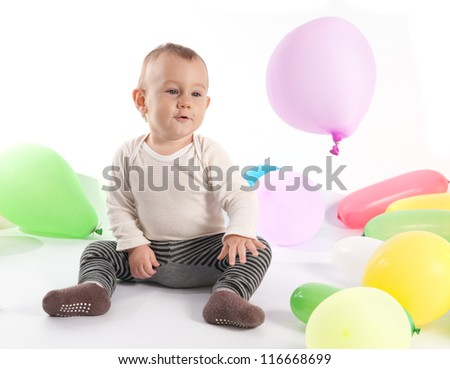 One year old baby boy playing with balloons - stock photo
