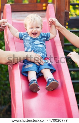 One year old Baby boy Sliding Down Slide with Parents. Happy little blond child with blue eyes having fun outdoor