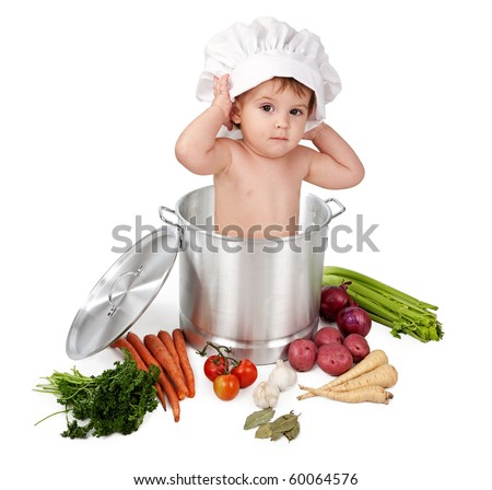 One year old baby boy wearing a chef hat in a large cooking pot with assorted vegetables around it