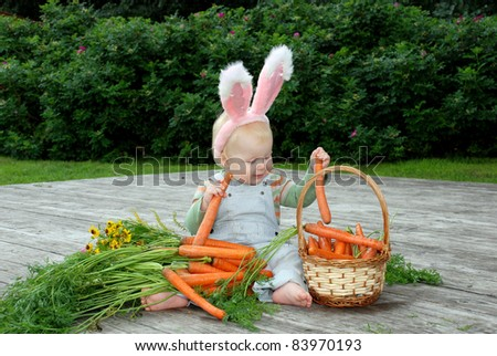 One year old baby dressed in bunny ears, holding a carrot; basket with carrot - stock photo