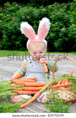 One year old baby dressed in bunny ears, holding and eating a carrot; basket with carrot