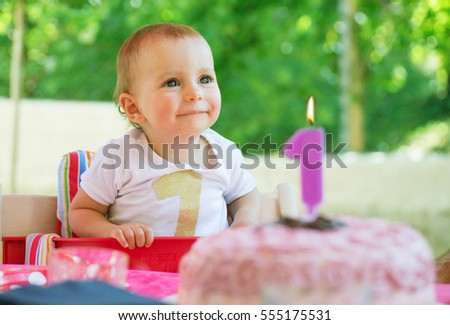 One year old baby girl celebrating her first birthday eating cake