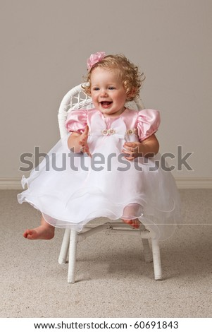 One year old baby girl wearing white and pink dress sitting in a white wicker chair. - stock photo