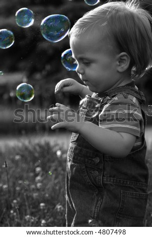 One year-old  baby in overalls with Bubbles, selective color Nice Spring Image - stock photo