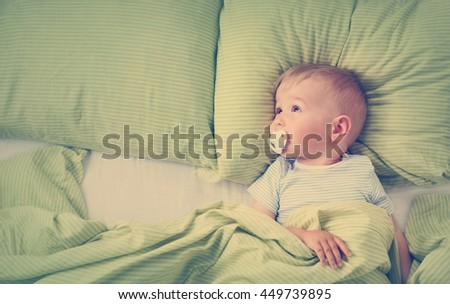 One year old baby lying in the bed with green bedding - stock photo