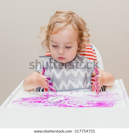 One year old baby sitting on the highchair with tray, examine fingers, finger paint and his own possibility to draw and making a mess.