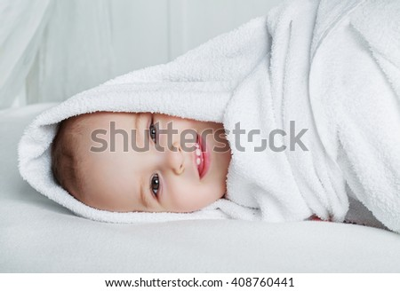 one year old baby with a towel in bed at home - stock photo
