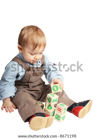 One-year old boy plays cubes - stock photo