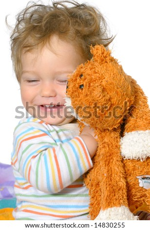 one year old boy with curly hair is hugging his ginger cat; isolated on white - stock photo