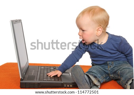 One year old boy with laptop - stock photo