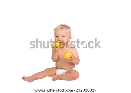One year old boy with lemon on white background