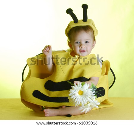 one year old child dressed up like a bee on yellow background - stock photo