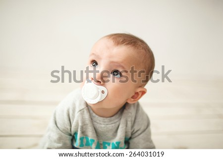 One year old cute baby boy sitting on rustic wooden floor over white background