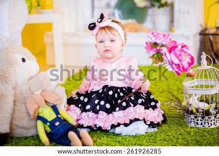 one year old girl in a pink dress sits in interior with Easter Bunny - stock photo