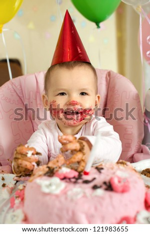 one-year-old little girl with  dirty-faced solemnize birthday, happy laughter, vertical photo