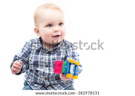 One year old white smiling baby boy holding colorful toy car in hand, isolated on white background, horizontal photo - stock photo