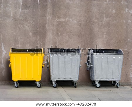 one yellow and two zinc garbage tanks near the wall - stock photo