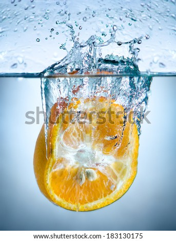 one yellow orange drop in blue water with splashes - stock photo