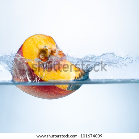 one yellow peach big  strawberry  drop in blue water with splashes - stock photo