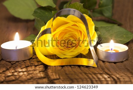One yellow rose blossom and two tea lights with metal heart shape on wooden board - stock photo