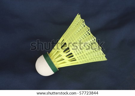 One yellow shuttlecock isolated on dark blue background - stock photo