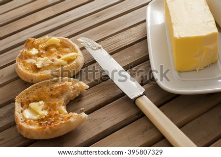 One yellow stick of butter on a white tray beside a knife and two toasted english muffins set on table made of wooden slats - stock photo