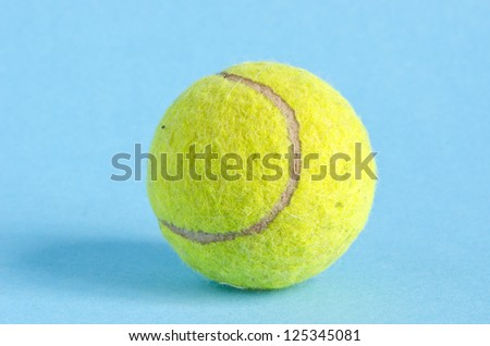 one yellow  tennis ball on azure background