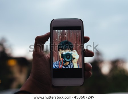 one young adult asian man shooting himself, take a selfie alone with smart phone and camera, relax on travel alone man in selfie action - stock photo