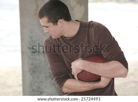 one young athletic man holding a football on the beach