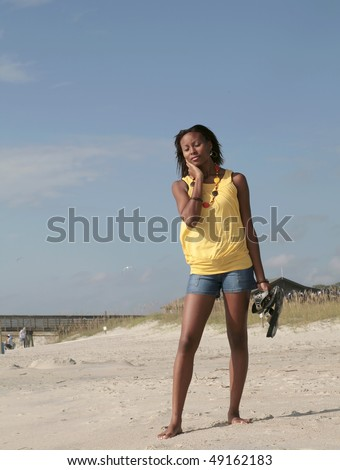 one young attractive African American female standing against blue sky on the beach looking very hot or unhappy - stock photo