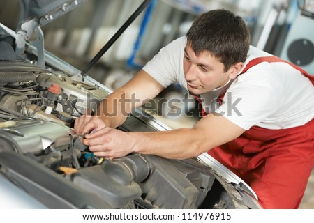 One young auto mechanic tighten screw with spanner during automobile car maintenance at engine repair service station - stock photo