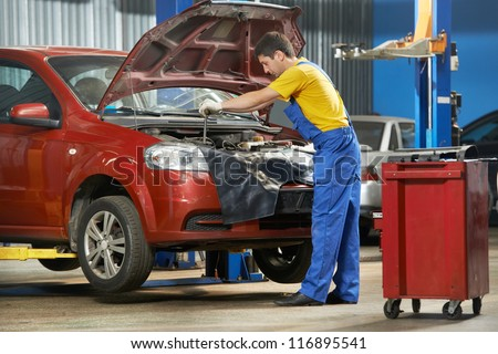 One young auto mechanic tighten screw with spanner during automobile car maintenance at engine auto repair shop service station - stock photo
