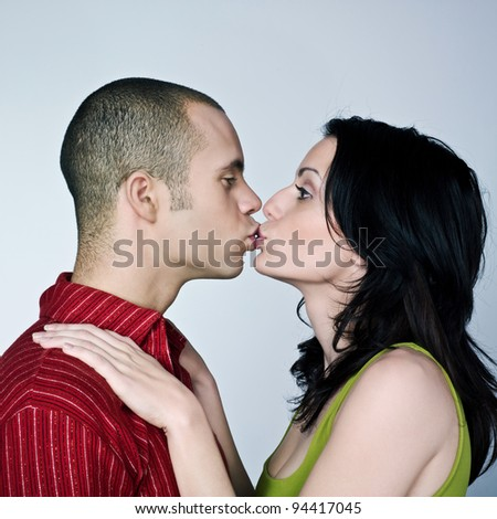 one young couple hugging kissing on studio isolated gray background - stock photo