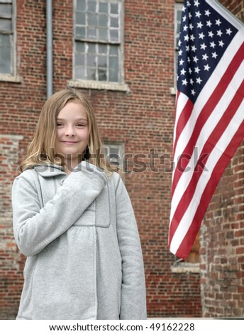 one young cute child with hand on her heart near an American Flag outdoors - stock photo