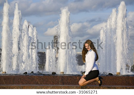 One young cute lady is sitting on her knees near the fountain in the park turning to the camera for making photo . - stock photo