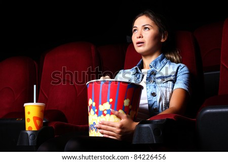 One young girl watching movie in cinema - stock photo