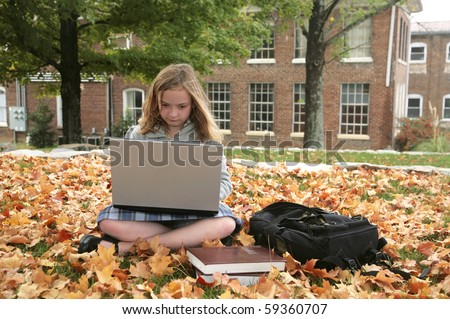 one young grade school student studying outdoors on a laptop in autumn - stock photo