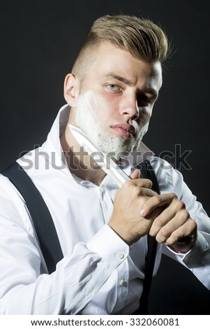 One young handsome sensual man shaving his face with knife and foam looking at camera with unbutton collar keeping his shirt stays in studio on black background, vertical picture