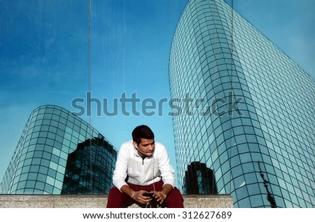 One young Indian business man talks on a smartphone outdoors  alone in city financial district street. Mobile communication concept - stock photo