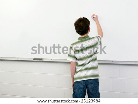 one young male student in a classroom writing on a whiteboard - stock photo