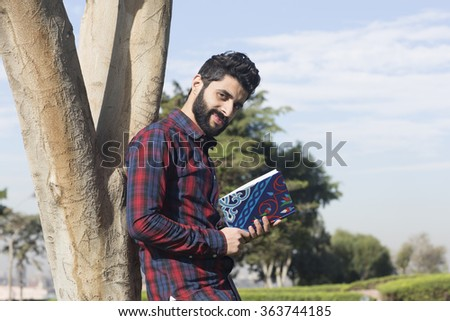 One young man is reading a book while sitting on his garden theme concept in Cairo Egypt in Middle East Africa  - stock photo