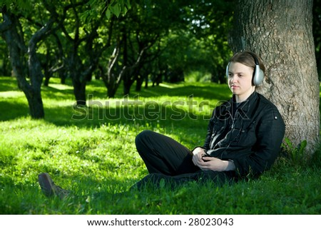 One young man is sitting on the grass under the tree listening to the music through the headphones.
