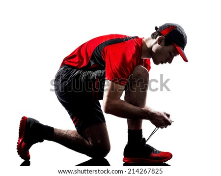 one young man runner jogger lacing shoes in silhouette isolated on white background - stock photo