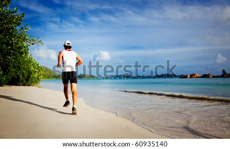 One young man running on a tropical empty beach at sunrise, rear view ; Seychelles, Indian ocean - stock photo