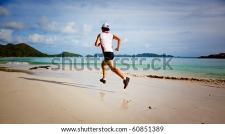 One young man running on a tropical empty beach at sunrise; Seychelles, Indian ocean - stock photo