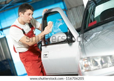 One young service mechanic cleaning automobile car door glass at auto repair shop - stock photo