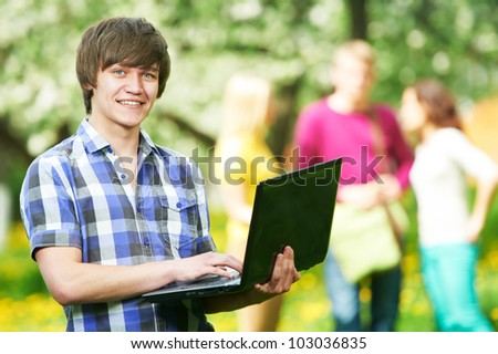 One young smiling happy student with laptop in front of young people group at spring outdoors - stock photo