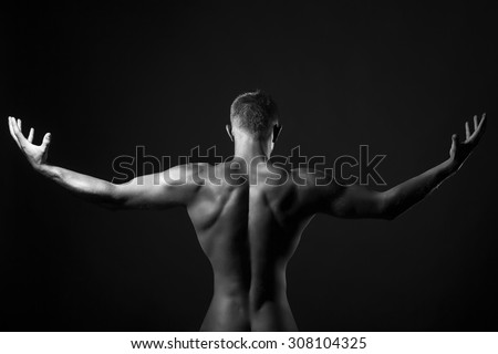 One young undressed boy with sexual strong muscular attractive body with raised arms in sides and beautiful back standing in studio black and white, horizontal picture